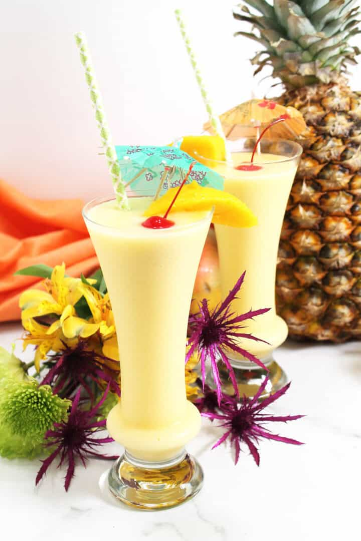 Two mango coladas garnished with cherry among flowers.