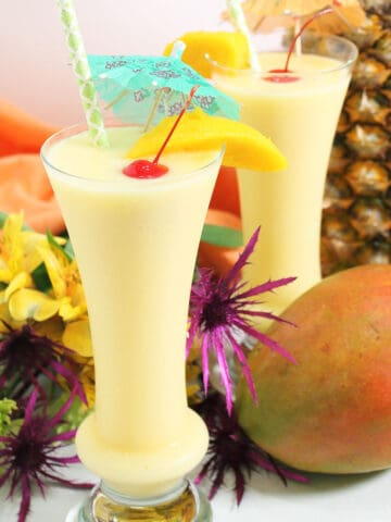 Two pina colada with mango cocktails with umbrellas near mango and pineapple.