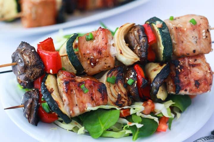 Closeup of 2 grilled pork kabobs on top of salad.