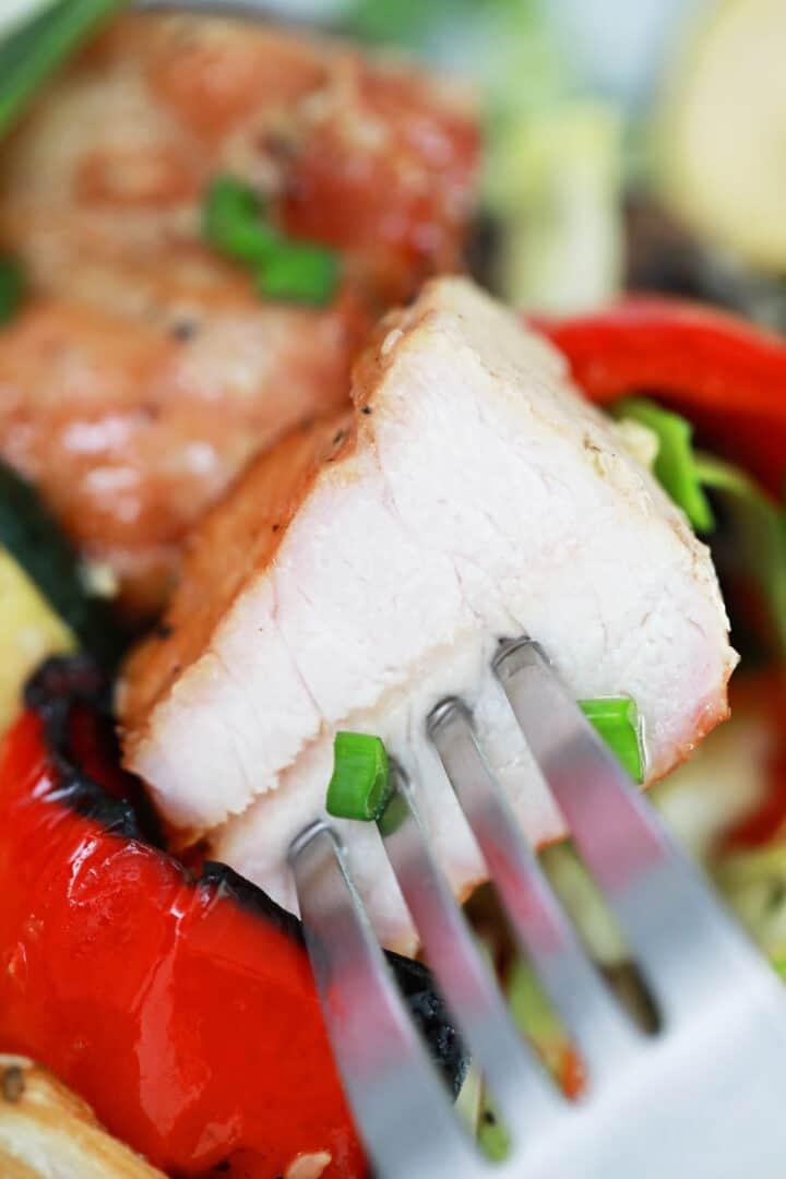 Closeup of bite of pork on fork over kabobs.