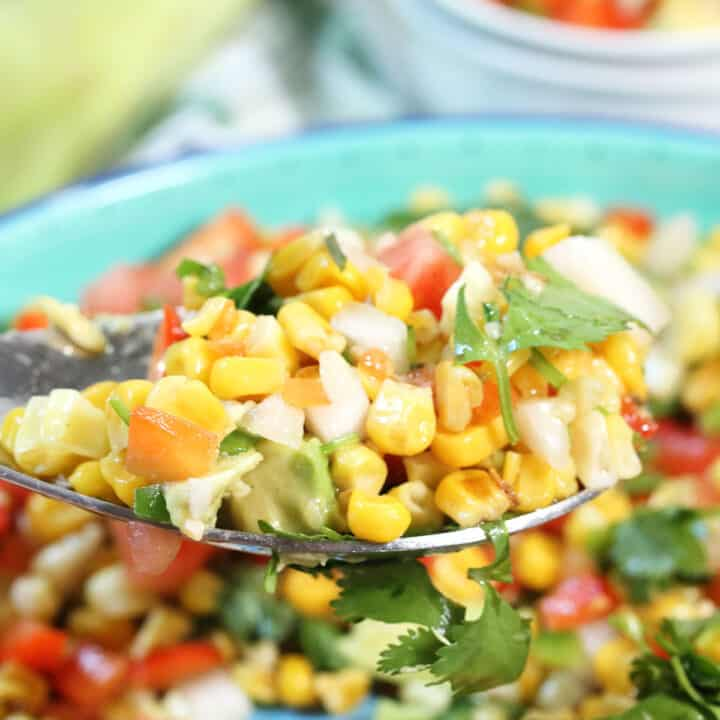 Closeup of spoonful of corn and avocado salad over serving bowl.