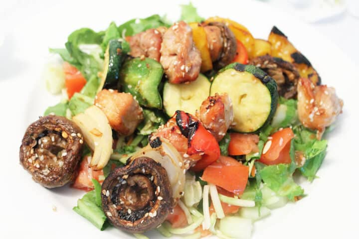 Korean BBQ Kabobs unskewered and served over salad.
