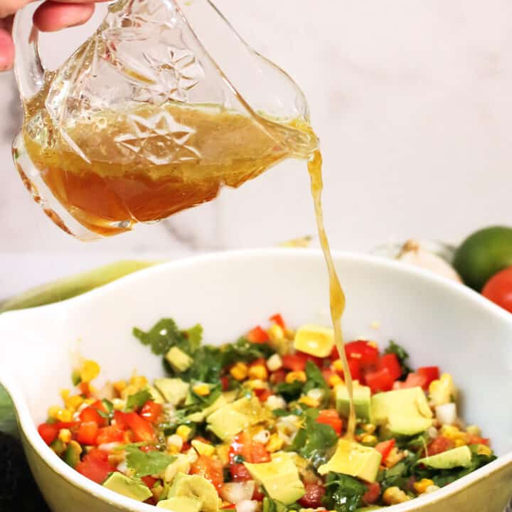 Pouring dressing over roasted corn salad.
