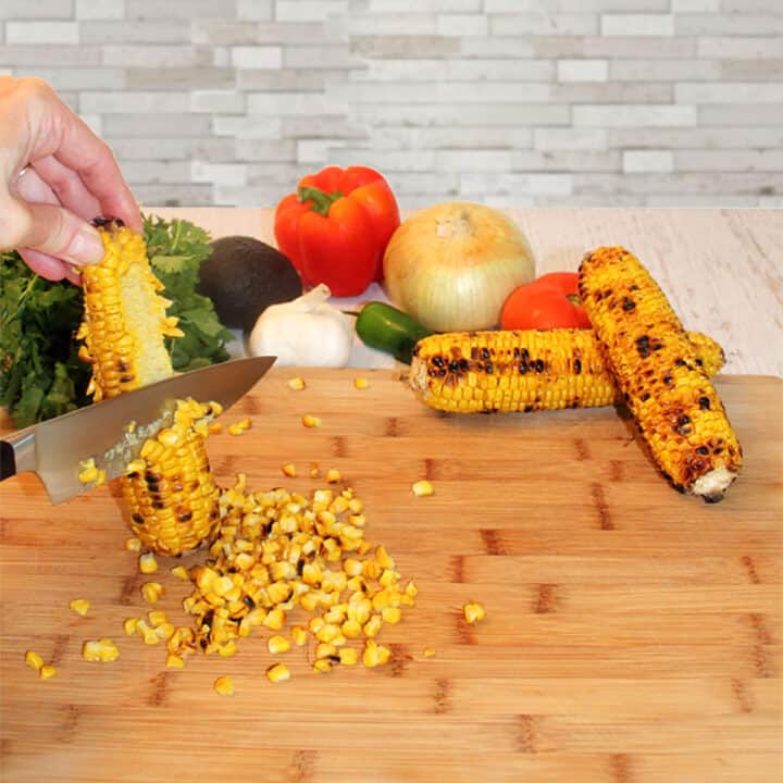Cutting grilled corn off the cob.