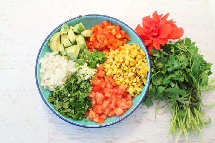 Salad ingredients laid out in blue bowl.