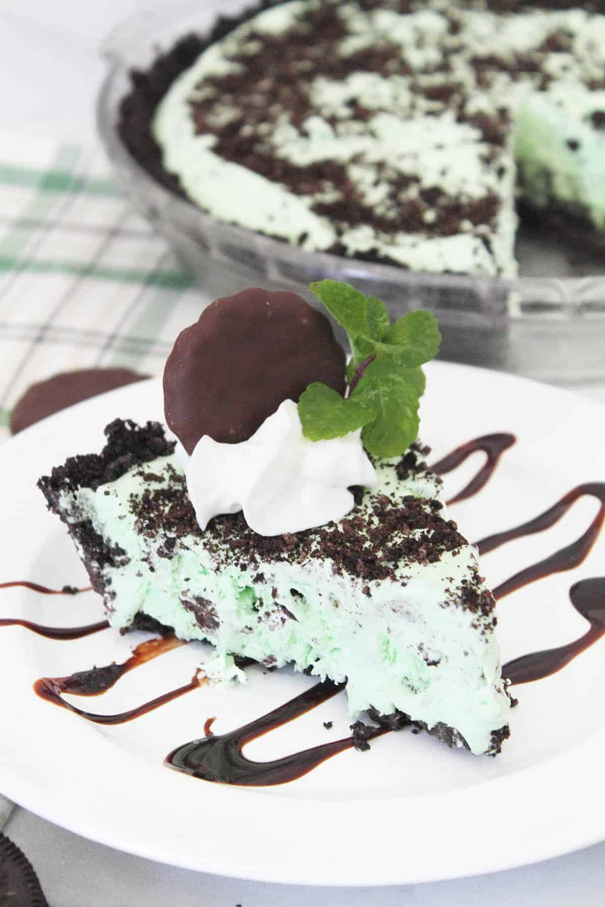 Slice of grasshopper pie on chocolate decorated plate with whole pie in back.