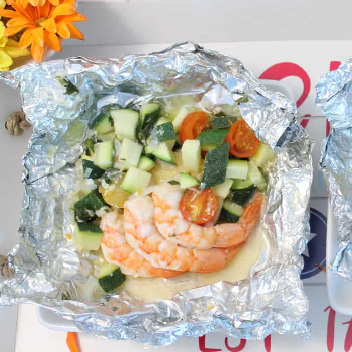 Opened foil packet with cooked shrimp and vegetables
