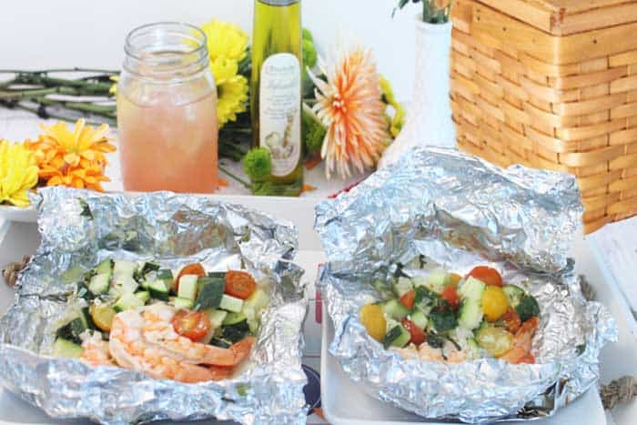 2 shrimp dinners in foil, unwrapped and ready to eat with picnic basket and mason jar cocktail in background