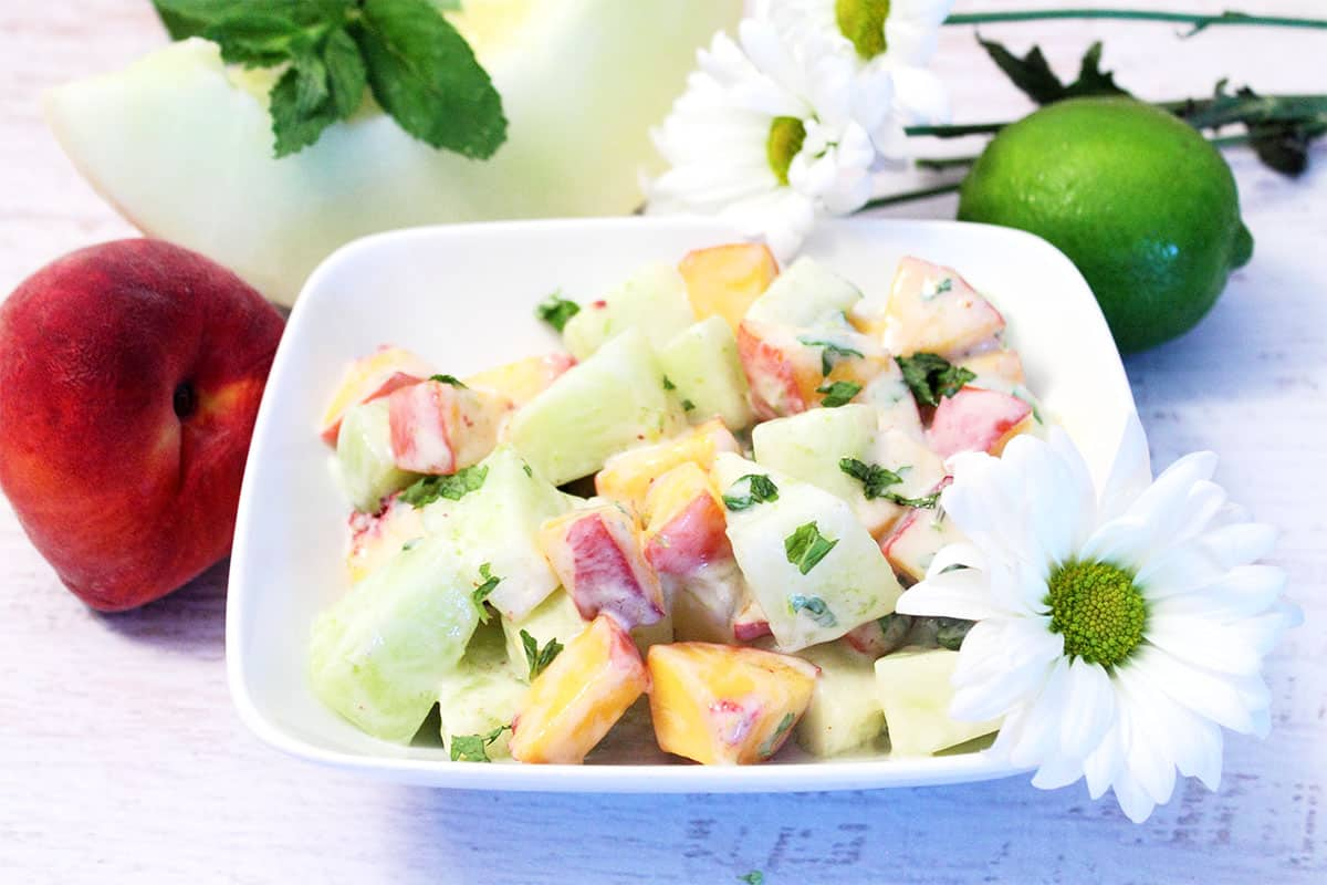 Honeydew Salad with peaches, melon and daisies around it.