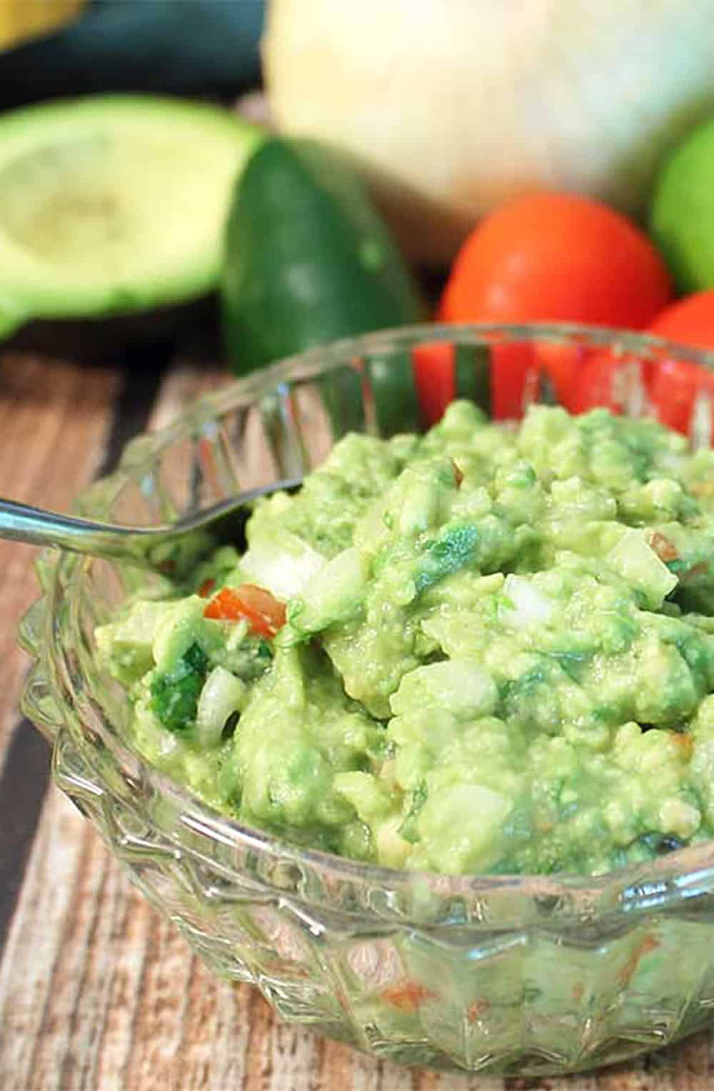 Bowl of guacamole closeup with ingredients in background.