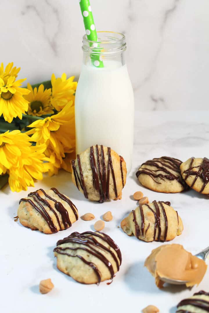 Cookies on white table with one leaning on milk bottle and daisies.