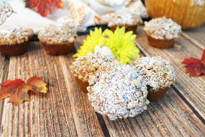 pumpkin muffins on wooden table with fall leaves around.