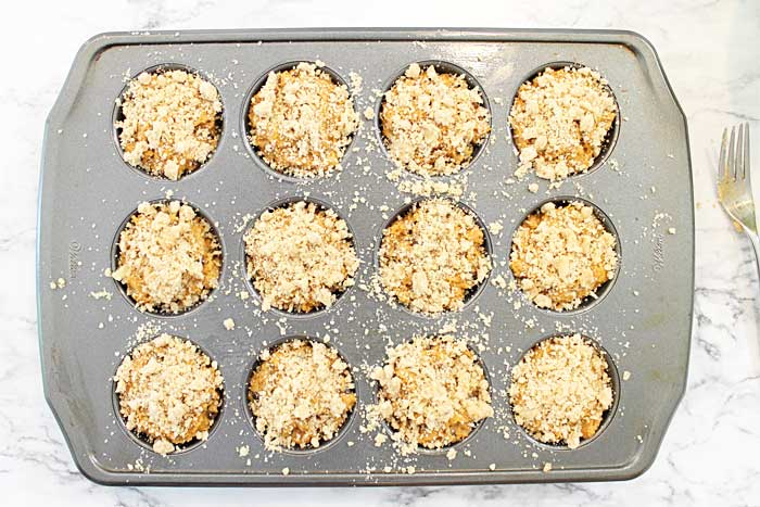 pumpkin muffins with crumbs in cupcake pan ready for oven.