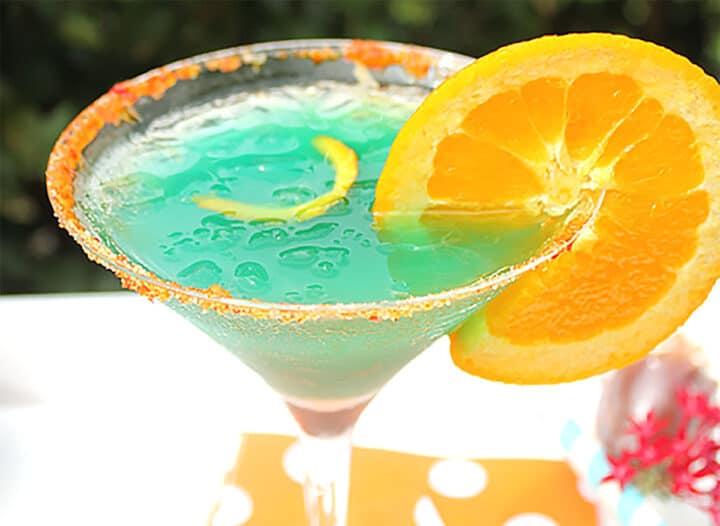 Blue curacao cocktail with orange garnish closeup.
