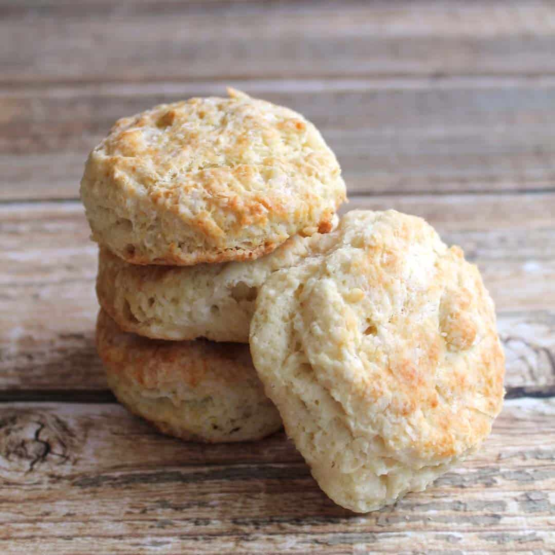 Stacked buttermilk biscuits with one leaning on stack on wooden table.