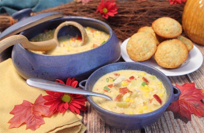 Corn chowder in blue bowl with corn muffins and larger bowl with ladle.