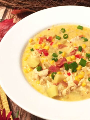 Chicken chowder in white bowl with gold napkin and fall leaves.