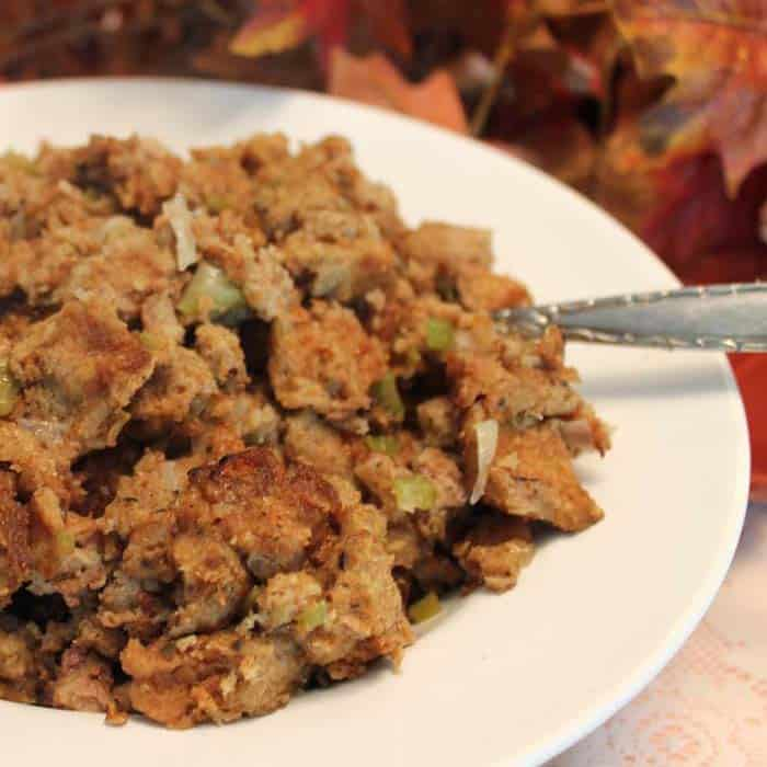 turkey stuffing in white bowl with fall leaves in background.