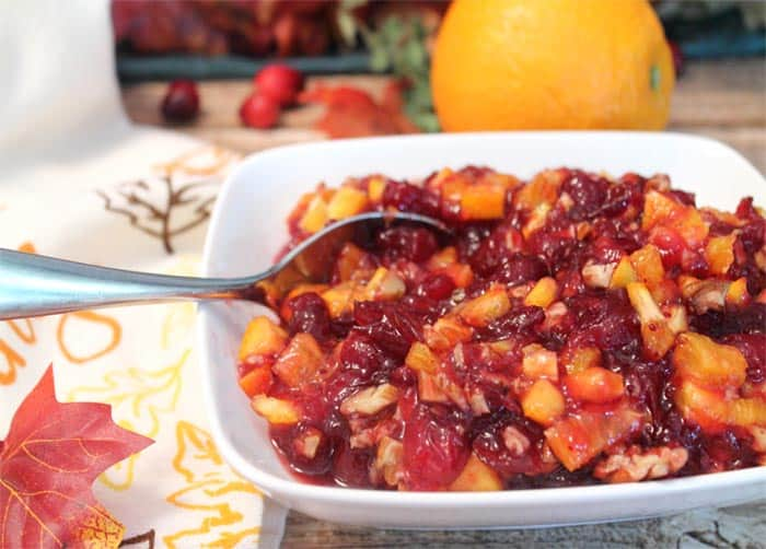 Cranberry Orange Relish in white bowl with spoon in it.