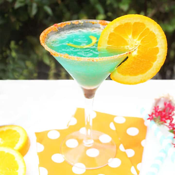 Single curacao cocktail on orange polka dotted napkins.