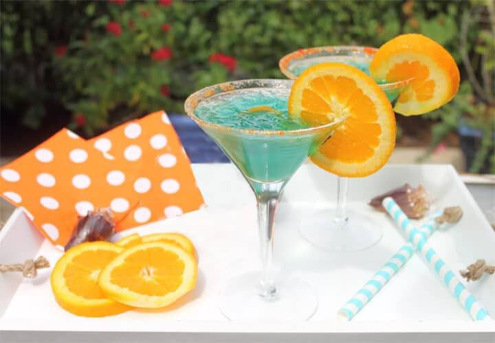 Two blue cocktails on wooden tray with striped straws.