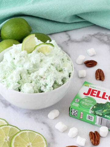 Bowl of green fluff in white bowl with limes in back.