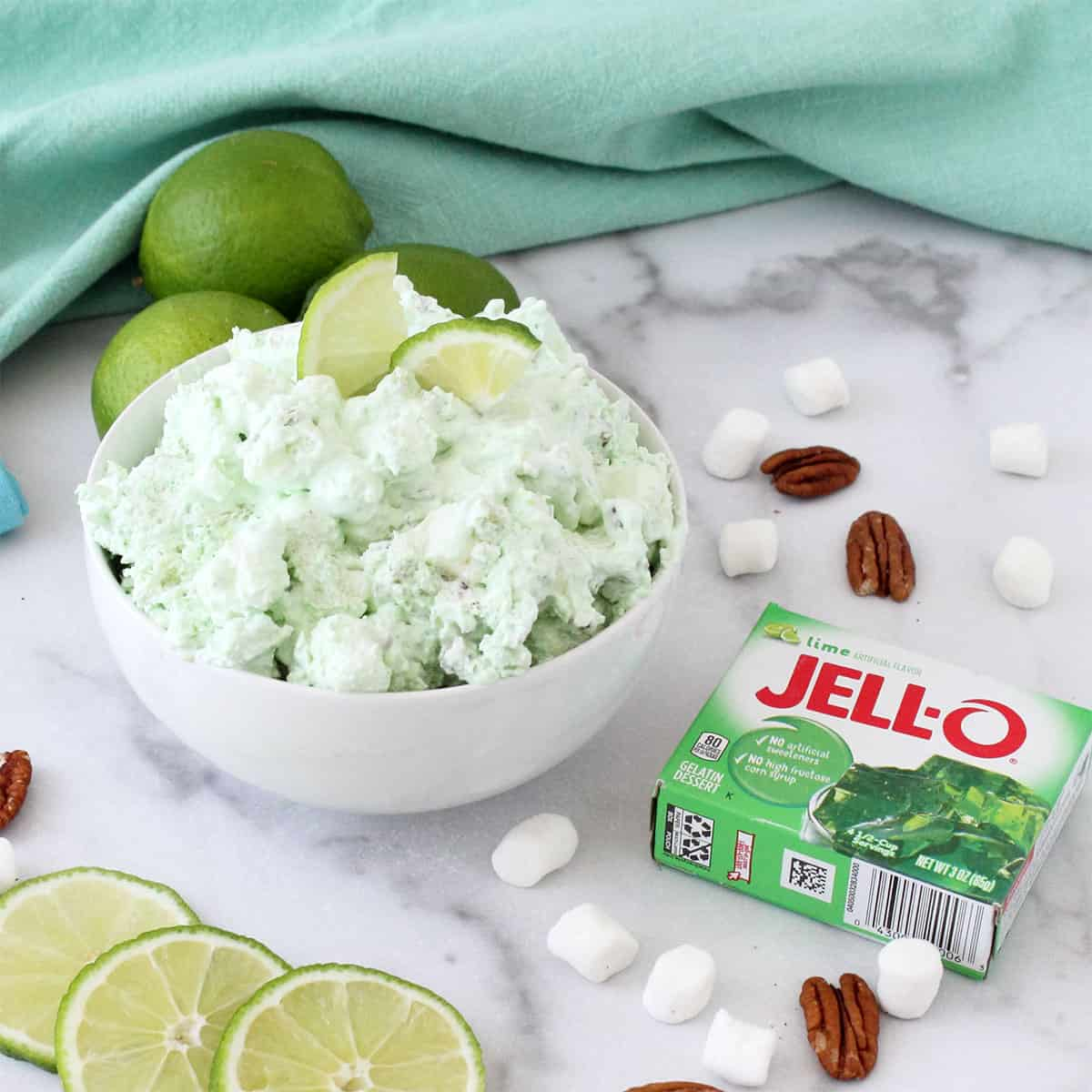 Bowl of lime jello salad in white bowl with limes in back.