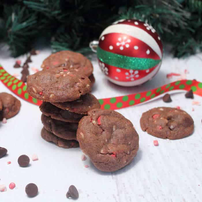 A stack of cookies on white table with Christmas ornament and greenery in back.