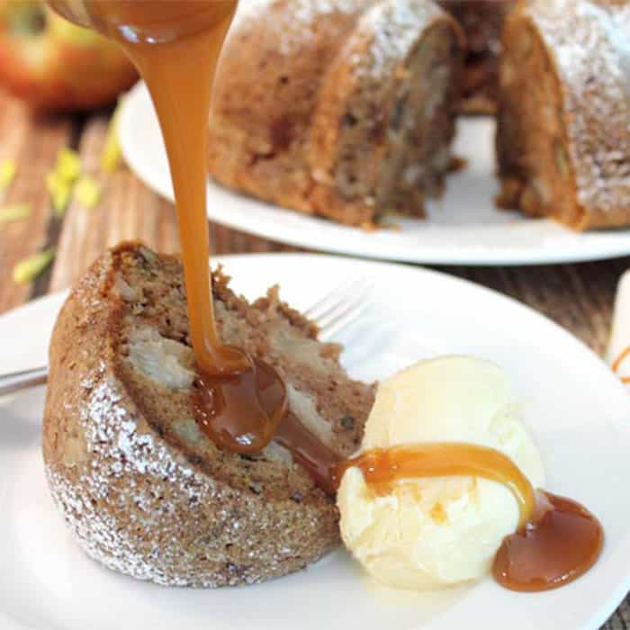 Pouring caramel sauce over apple cake on white plate.