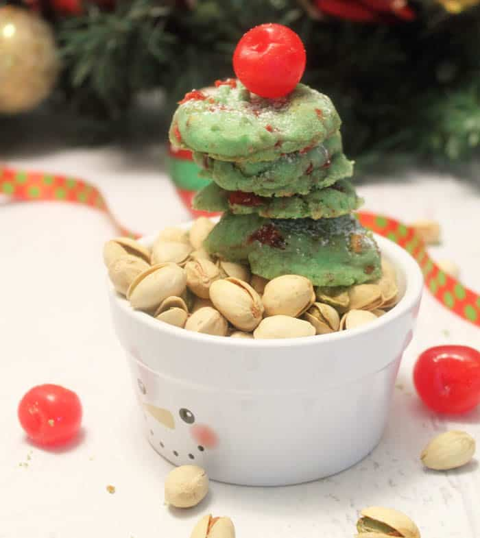 Pistachio cookies stacked in snowman bowl with cherry on top and pistachios around base.