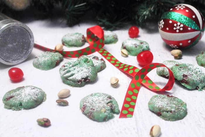 Pistachio Cherry Meltaway Cookies scattered on white table with red ribbon and greenery in back.