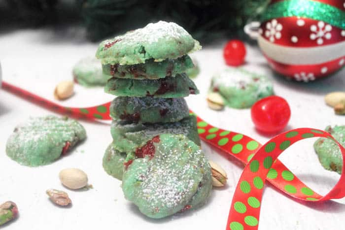 Stack of cookies on white table with red and green Christmas ribbon.