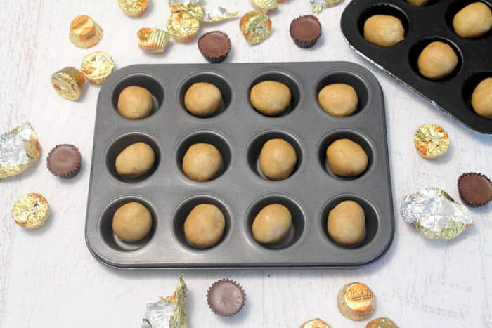 Preparing cookie cups by pressing into muffin pan.