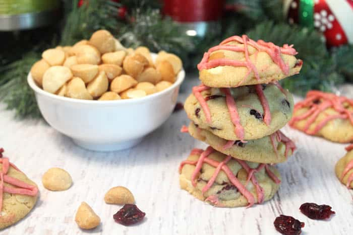 Stacked white chocolate cranberry cookies beside a bowl of macadamia nuts.