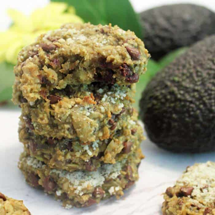 Stacked oatmeal cookies on white table with avocado next to them.