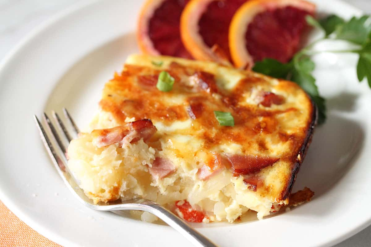 Slice of casserole on white plate with bite on fork.