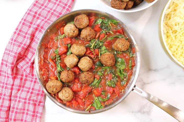 Adding meatballs to tomato sauce in skillet.