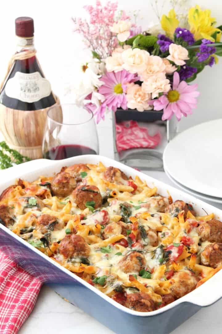 Baked meatball casserole with wine and flowers behind it.