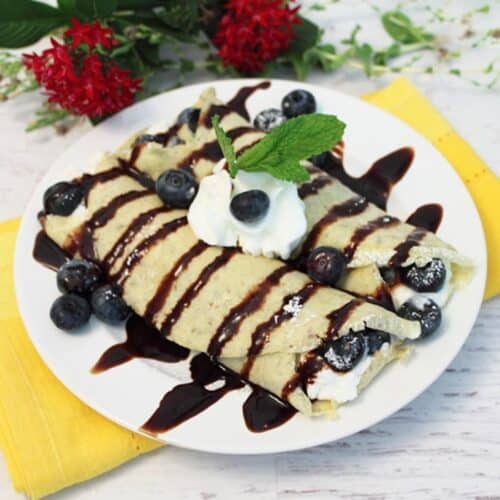 Plated sweet crepes with chocolate drizzle and whipped cream on top.