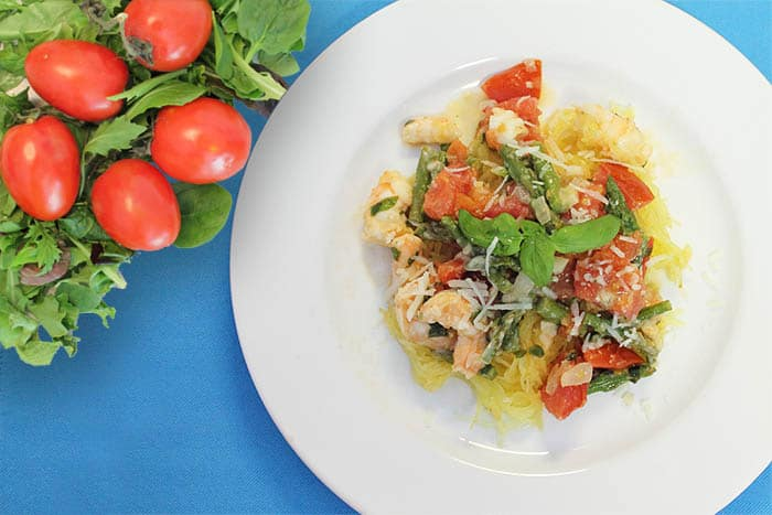 Shrimp Primavera on a white plate with blue placemat and tomatoes on the side