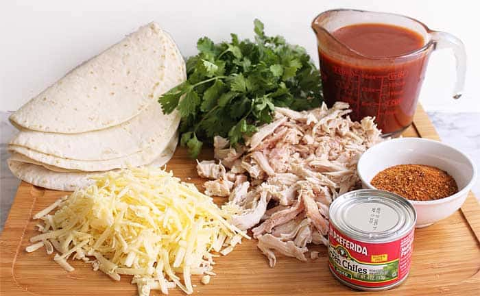 Ingredients for enchiladas on wooden board.