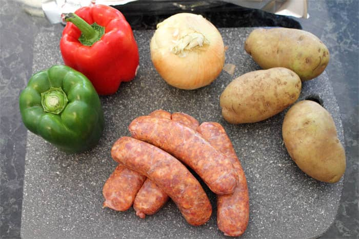 Sheet Pan Dinner ingredients or peppers, onions, potatoes and Italian sausage.