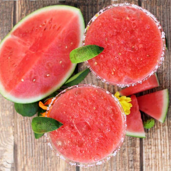 Overhead of 2 frozen margaritas with slice of watermelon.