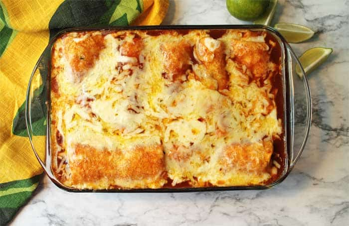 Baked casserole overhead with colorful towel and limes in background.