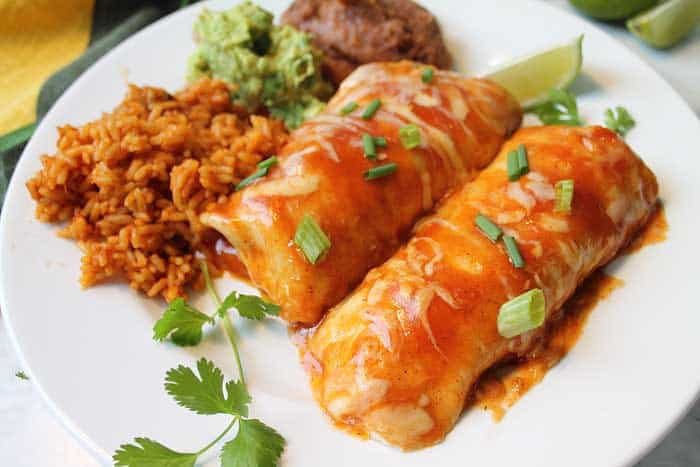 enchiladas on plate with rice beans and guacamole