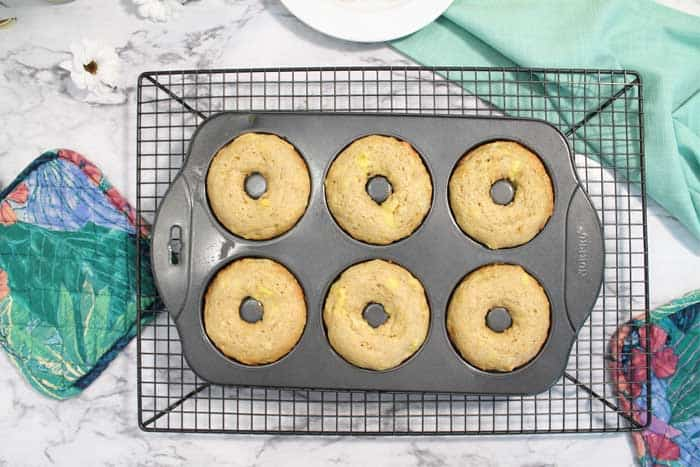 Baked doughnuts in doughnut pan cooling on rack.