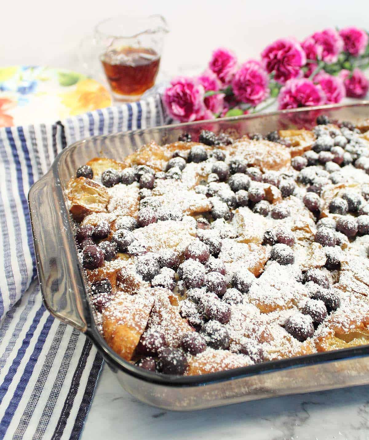 Overnight Blueberry French Toast Bake dusted with confectioner's sugar on white marble table with red flowers and maple syrup in background.
