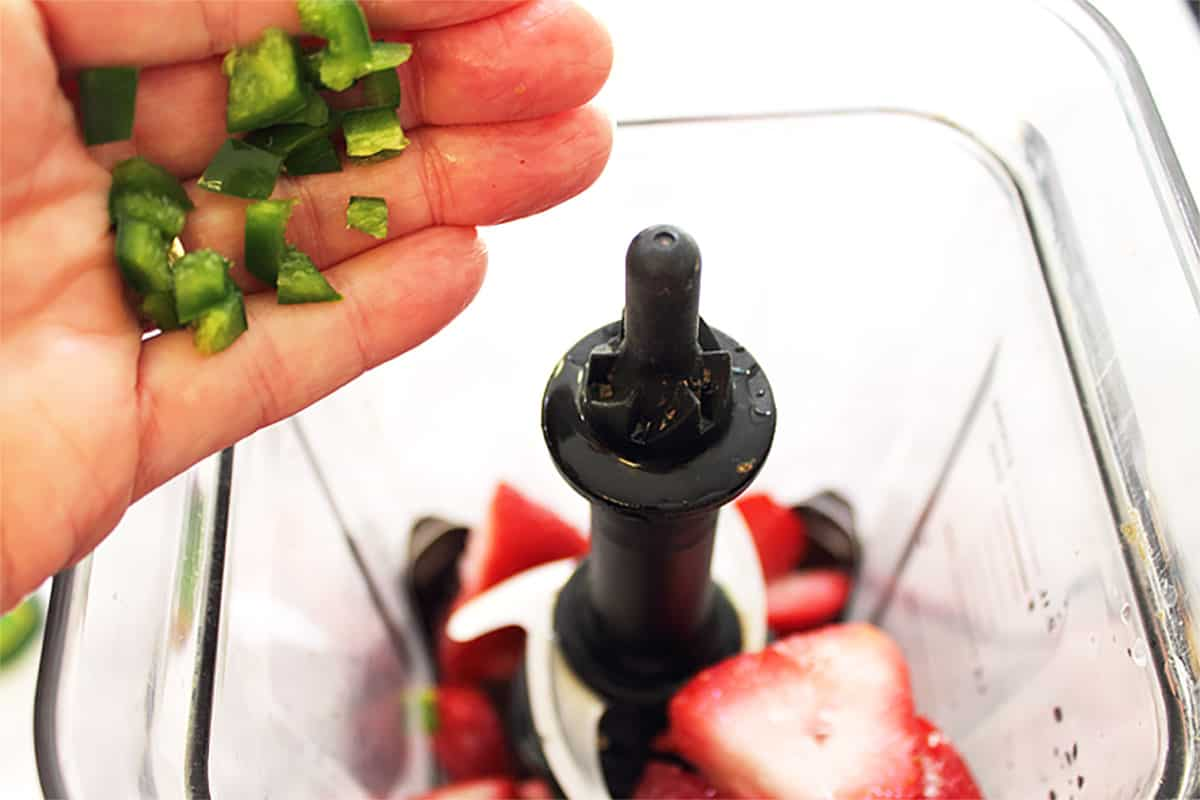 Adding jalapeno to strawberries in blender.