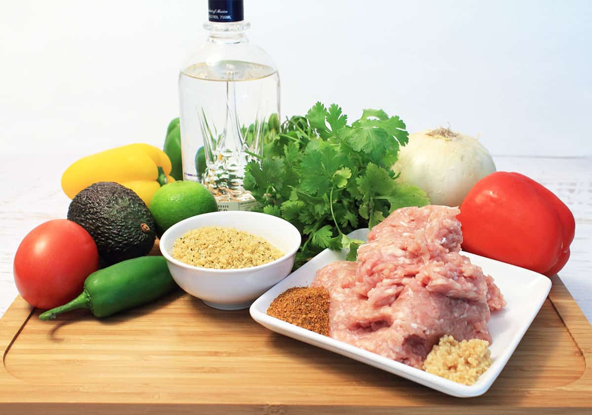 Ingredients on wooden cutting board including ground chicken onion red pepper cilantro jalapeno and tequila.