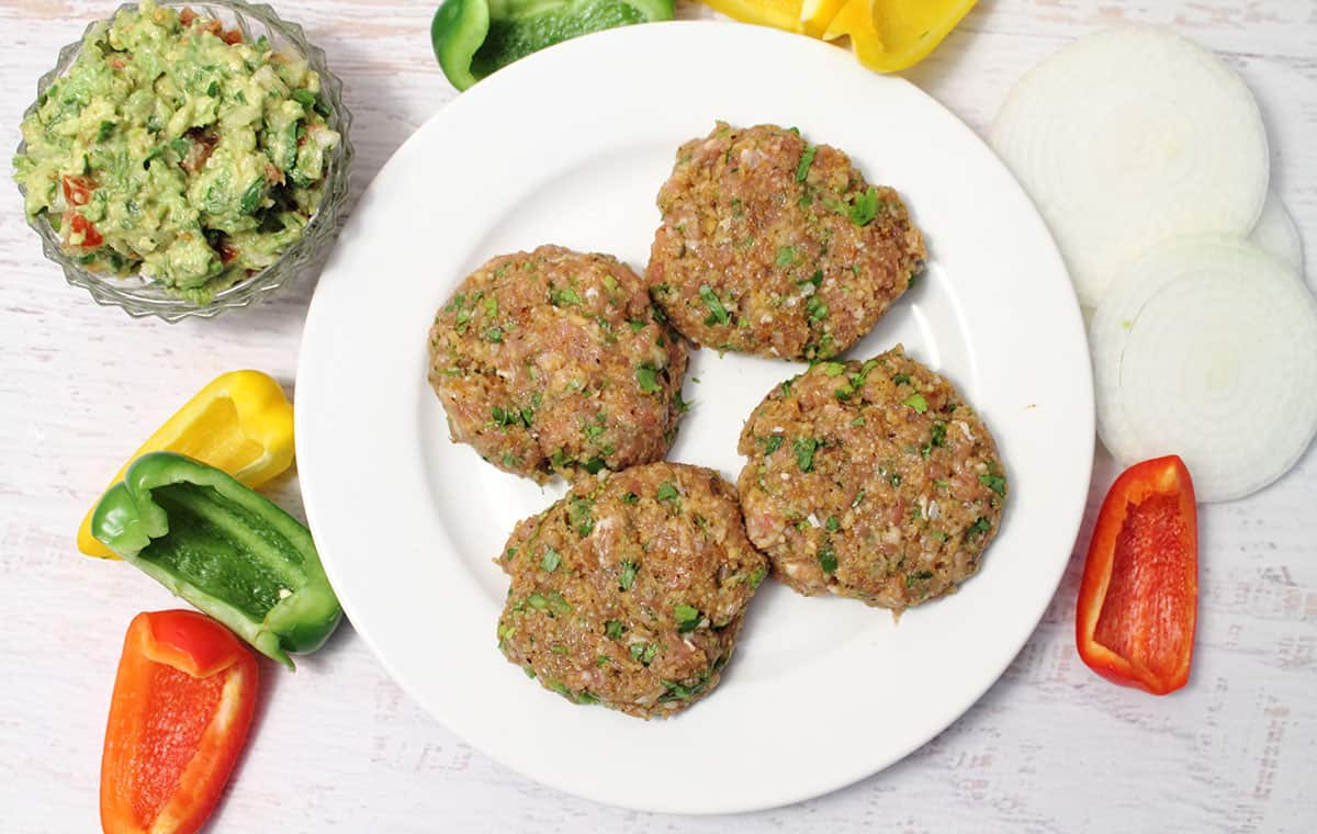 Prepared burgers on white plate surrounded by ingredients.